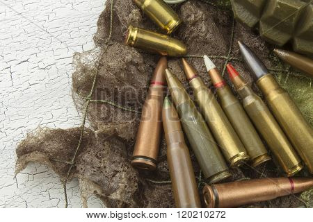 Different types of ammunition on a camouflage background. Preparing for war.