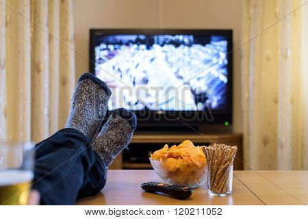 Man Watching Tv (news About Refugees Camp ) With Feet On Table