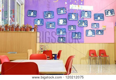 Kindergarten Class With Small Red Chairs And Children's Drawings On The Walls