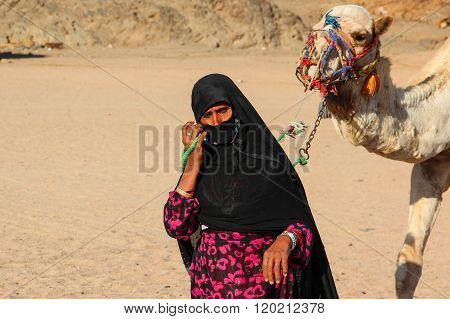 The old woman-cameleer from Bedouin village in Sahara desert with her camel