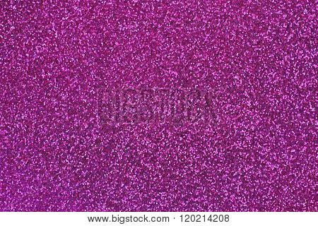 Closeup abstract background glittery texture photo of glitter in magenta shade