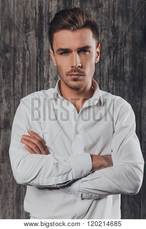 Handome Rigid Man In White Shirt On The Grey Background Crossing Hands
