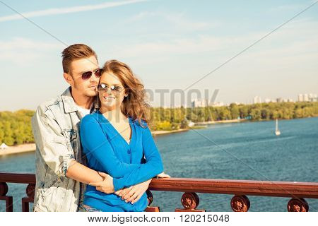 Happy Cheerful Couple In Love Embracing Each Other On The Bridge
