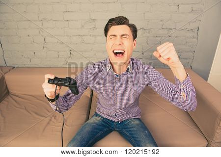 Happy Cheerful Man Triumphing With Raised Hand And Joystick