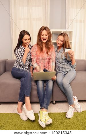 Three Laughing Women Sitting On Sofa With Laptop And Making Purchaces