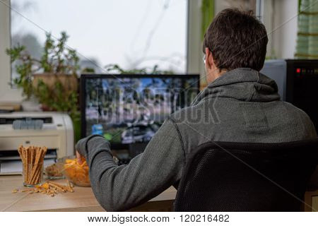 Male Gamer Playing Shooting Game On Computer With Snacks Lying On Table
