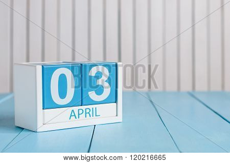 April 3rd. Image of april 3 wooden color calendar on white background.  Spring day, empty space for
