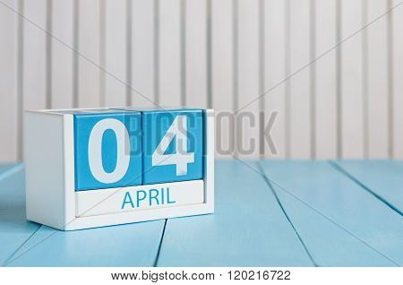 April 4th. Image of april 4 wooden color calendar on white background.  Spring day, empty space for