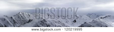 Panoramic View On High Snowy Mountains And Sunlight Storm Sky Before Blizzard