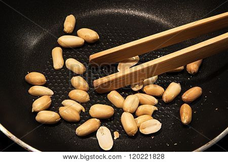 Peeled Peanuts Roasted In A Black Pan As A Snack Or To Cook Asian Satay Sauce