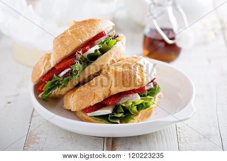 Croissant sandwich with brie, salad and strawberry