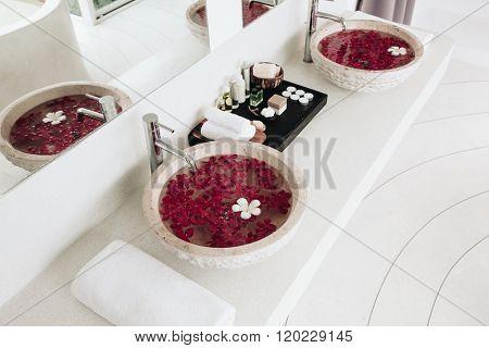 Luxury hotel bathroom details: sink with flowers, spa decoration