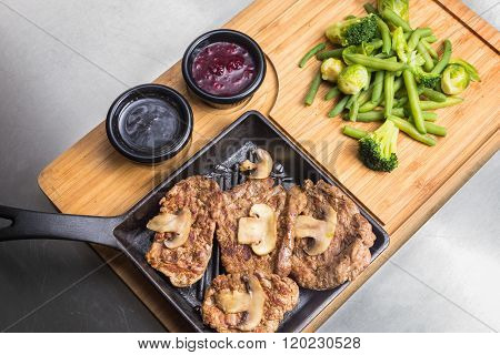 Fried Meat With Mushrooms, Sauses And Vegetables On Wooden Plate