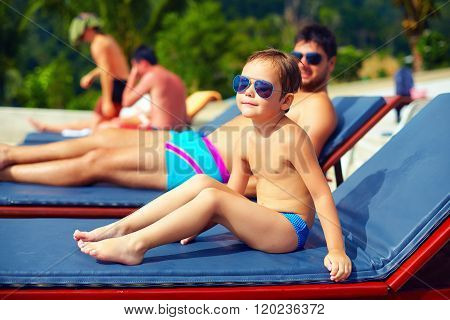 Cute Young Kid, Boy Relaxing On Lounge During Summer Vacation