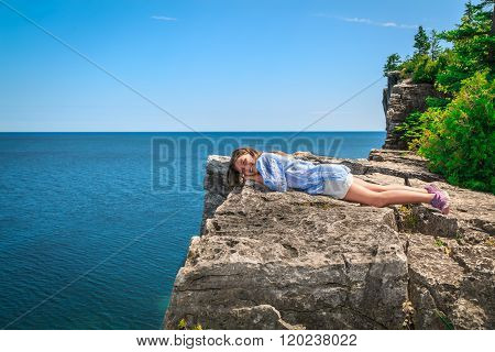 Happy, joyful little girl lying and relaxing on the edge of high cliff above gorgeous amazing Cyprus