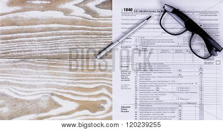 Faded White Desktop With Tax Form And Pen With Reading Glasses
