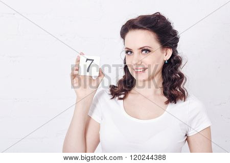 Girl In White T-shirt Holding Number Seven.