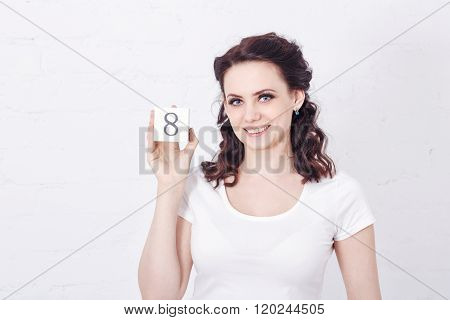 Girl In White T-shirt Holding Number Eight.