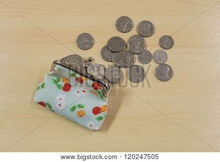 Coins With Open Money Bag On Wood Desk Background
