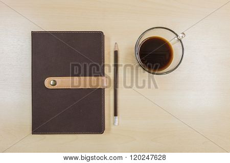 Brown Note Book , Pencil And Black Coffee In Work Concept