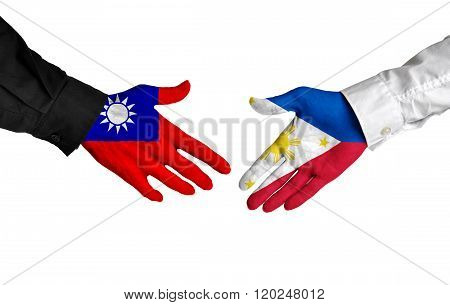 Taiwan and Philippines leaders shaking hands on a deal agreement