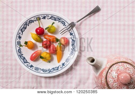 Sweet Dessert In Fruit Shape On Dish With Small Fork And Tea Pot On Pink Tablemat Background