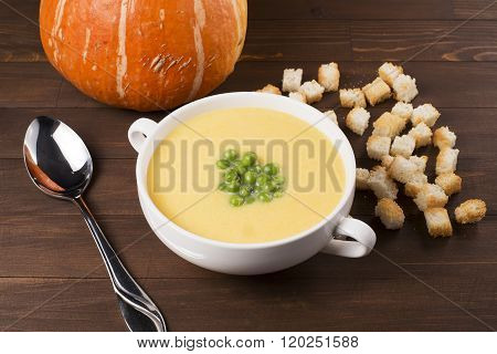 Cream Soup Of Pumpkin With Spices, With Cream, Croutons And Peas, On A Brown Wooden Table