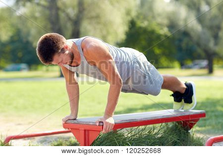 fitness, sport, exercising, training and lifestyle concept - young man doing push ups on bench at summer park