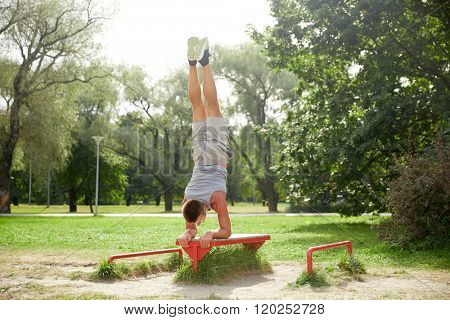 fitness, sport, training and lifestyle concept - young man exercising on bench at summer park