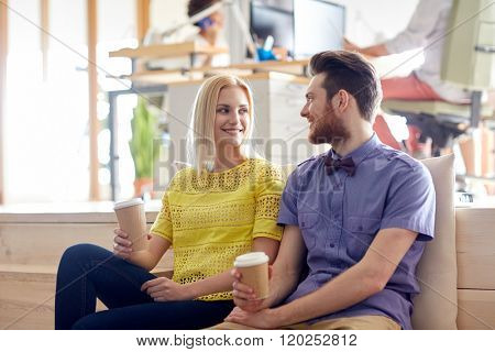 business, startup, people and communication concept - happy man and woman drinking coffee and talking in office