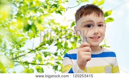 childhood, environment, ecology, discovery and people concept - happy little boy looking through magnifying glass over green natural background