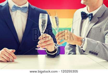 people, celebration, homosexuality, same-sex marriage and love concept - close up of happy married male gay couple drinking sparkling wine and clinking glasses on wedding over rainbow flag background