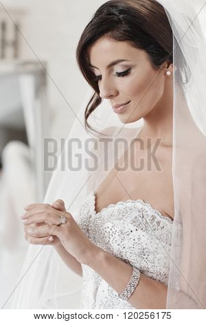 Portrait of beautiful young bride, looking at engagement ring, looking down.