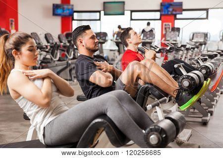 Three People Doing Crunches In A Gym