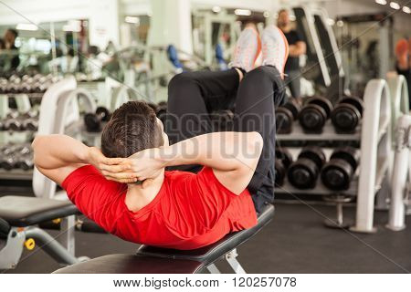 Young Man Doing Crunches On A Bench