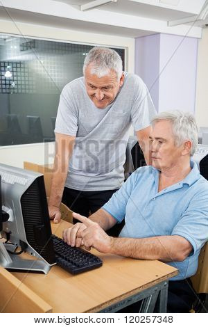 Senior Man With Classmate Using Computer In Class