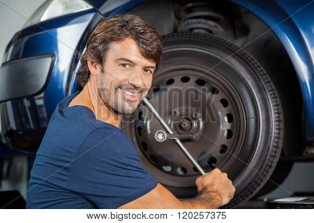Smiling Mechanic Fixing Car Tire With Rim Wrench