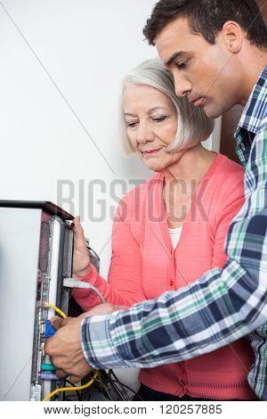 Tutor Assisting Senior Woman Setting Up Computer