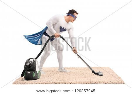 Young man in superhero costume vacuuming a carpet with a vacuum cleaner isolated on white background