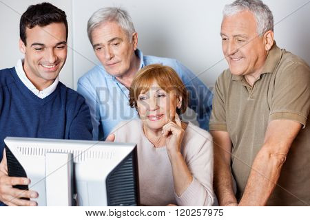 Teacher Assisting Senior People In Using Computer At Class