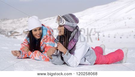 Giggling twins laying down at ski slope