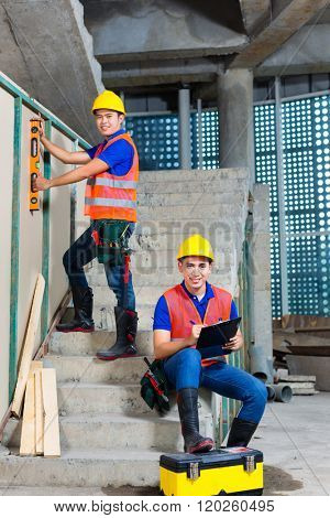 Asian Indonesian builder or craftsman with hardhats, checklist and a bubble level controlling or checking a walls of a tower building or construction site