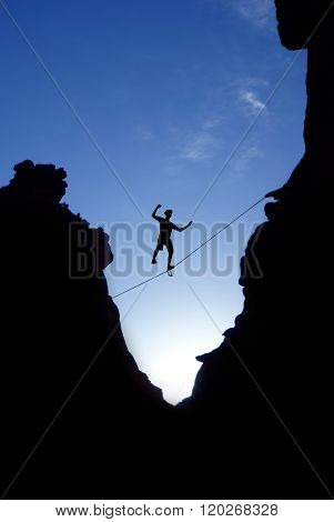 Man Walking On Tight Rope Over The Rock
