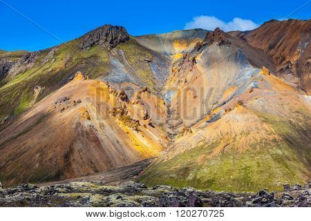 Travel to Iceland in the July. Summer volcanic tundra. Multi-colored mountains from rhyolite are lit with sun