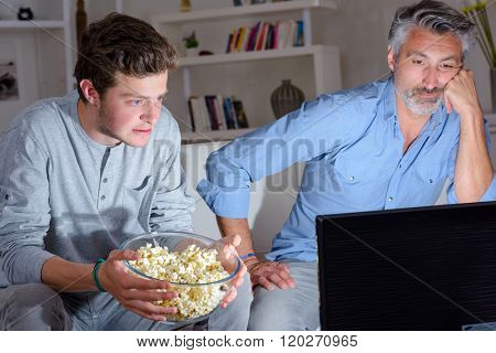 Two men watching television holding bowl of popcorn