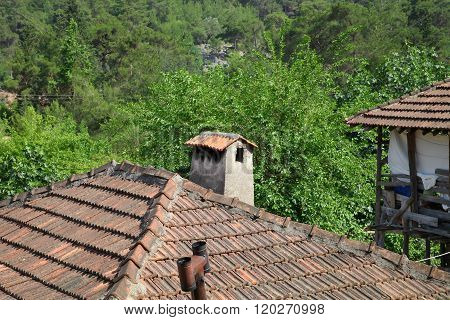 Old Tiled Roof With A Chimney In The Sun On The Forest Background