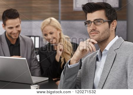 Young businessman sitting in office, thinking, looking away, colleagues working at background.