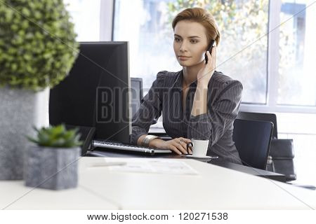 Attractive businesswoman working in green office, talking on mobilephone, using computer.