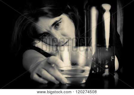 Drunk and depressed lonely woman holding a glass of whisky with a sad expression
