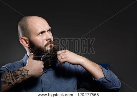 Man Cutting Beard Against A Grey Background